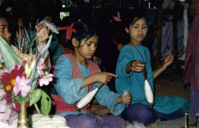 The younger girls use a distaff for spinning yarn